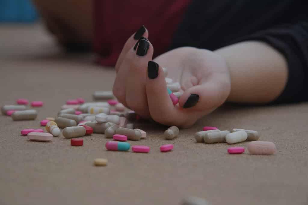 jovem caida com pílulas pelo chão denuciando abuso de substancia ou tentativa de suicidio