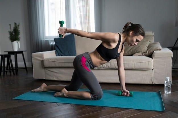Vista lateral da mulher fazendo exercícios com pesos em casa